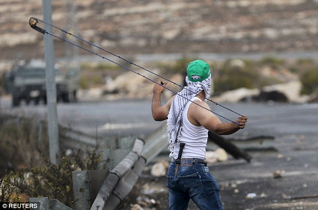 Ready for action: A slingshot throwers prepares to launch a stone during clashes with Israeli soldiers in Bet El