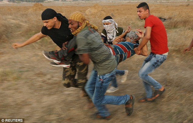 Helping hand: Four Palestinians rush an injured comrade away from the action near the Israeli border