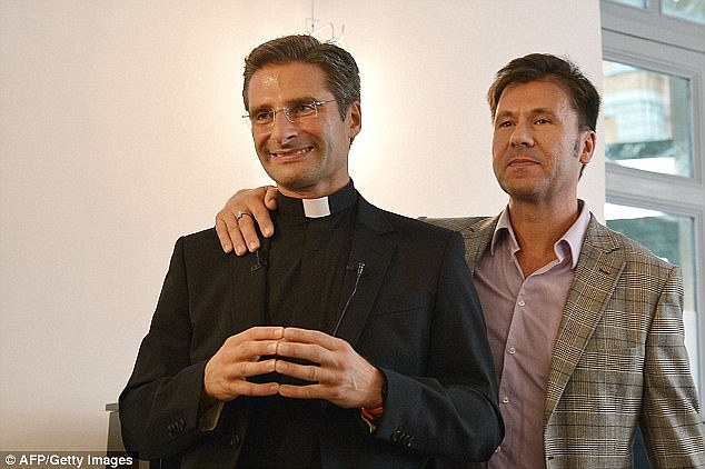 Polish priestKrzystof Charamsa (left)has accused the Catholic Church of making life 'hell' for millions of homosexuals after he was fired on the day he announced he was in a relationship with another man