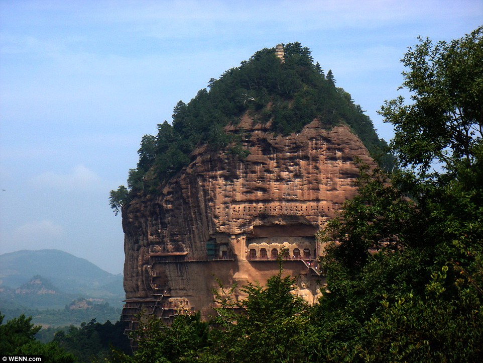 Looking like a scene from a movie, the Maijishan Grottoes, cut in the side of the hill of Majishan in Tianshui, Gansu Province, feature a stunning selection of murals and sculptures  surrounded by winding walkways and spiral stairs
