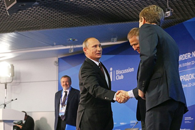 Iron grip: Jeremy Corbyn's pro-Kremlin aide Seumas Milne pictured shaking hands with the Russian President Vladimir Putin, at a propaganda summit in Sochi last year
