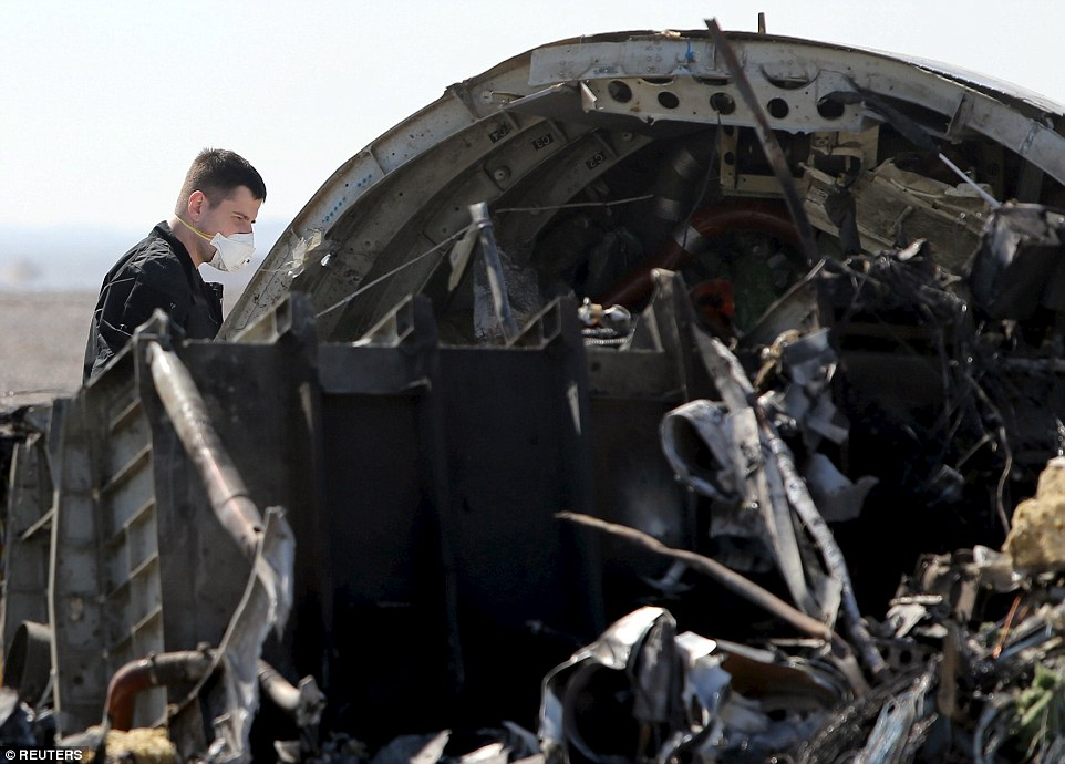 A Russian investigator looks closely at a large section of fuselage to inspect the nature of damage which led to the disaster