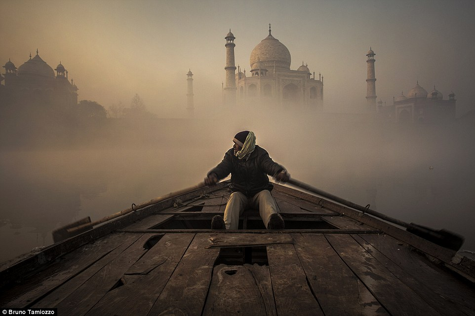 Travel - Honourable mention: The Yamuna River by Bruno Tamiozzo. The 'Yamuna' River is the largest tributary of the Sacred river Ganges and is venerated by the Hindus. According to Hindu mythology, in fact, Yamuna is Surya's daughter and sister of Yama, the god of death. Very close to the 'Taj Mahal', in the city of Agra, the only way to reach the 'prohibited' shore of the river, is a very old wooden boat. The sunrise is one of the quieter moments to navigate on the river, and the climatic conditions create mysterious and extremely fascinating atmospheres