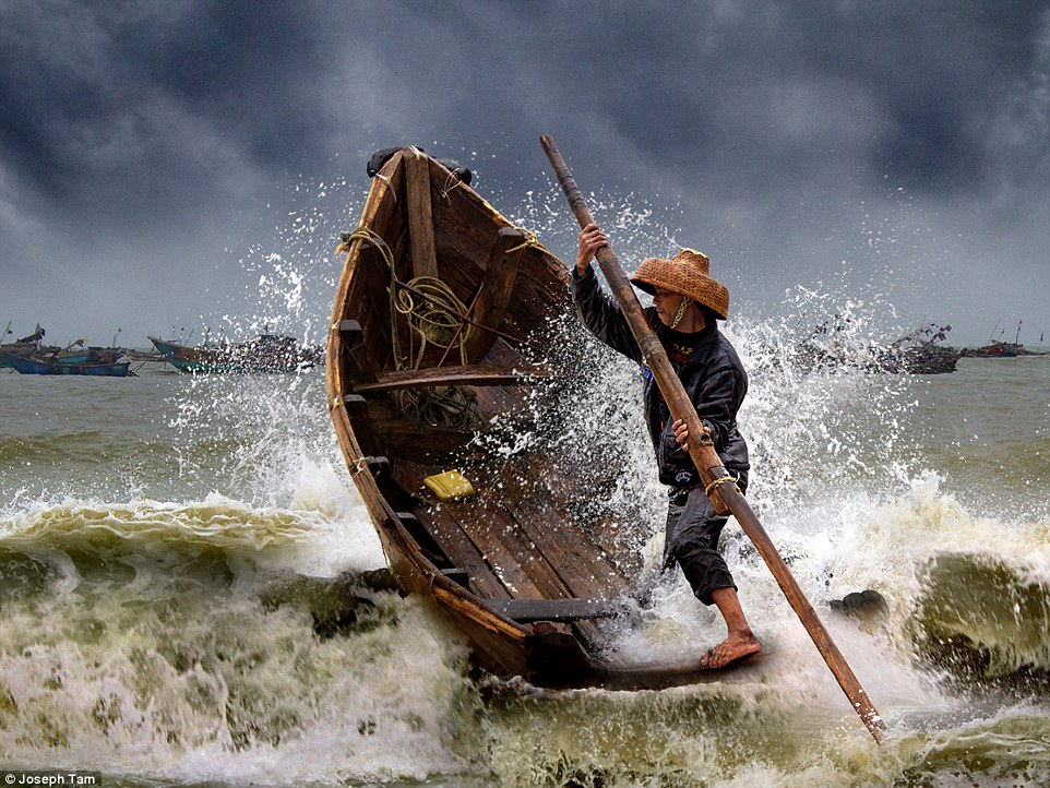Open colour - Honourable mention: Braving the storm, by Joseph Tam. 'This shot was taken from a fishing village in Dianbai, in China's Guangdong province. The fisherman in the timber boat is a courier who brings the catches from fishing boats to shore regularly. The swirling threat of the storm clouds and thunderous clamour of the angry waves sends a foreboding message to most'