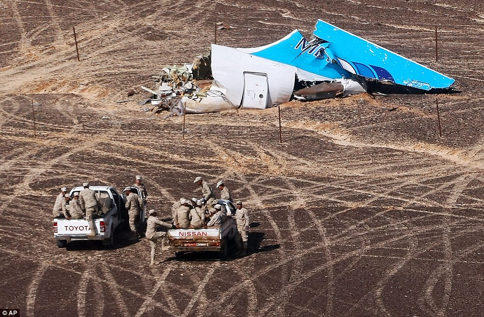 Egyptian military approach a plane's tail at the wreckage of a passenger jet bound for St Petersburg in Russia that crashed in Hassana