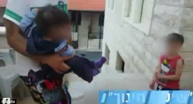 Screaming: The tiny infant was picked up by her father, in the footage filmed in the Israelicity of Abu Gosh, west of Jerusalem, before being forced into a bucket