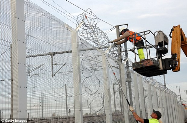 Workers reinforce a fence with razor wire to protect the Eurotunnel site from migrants who attempt to reach the UK, as it is revealed France is planning ontemporarily re-introducing passport controls at all its borders