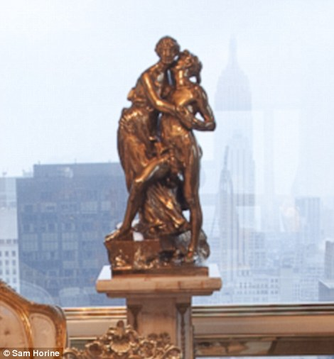Risqué business: The bronze statue that sits behind Melania Trump's desk is quite racy for a home office, with a man caressing a woman and the man planting a kiss on the woman's neck