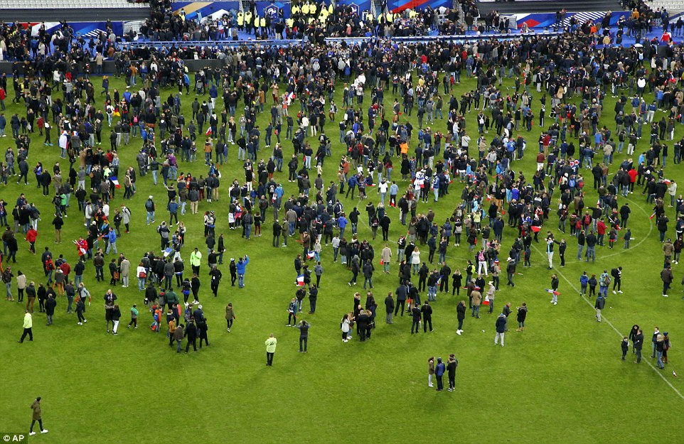 Spectators invade the pitch of the Stade de France stadium after two explosions were heard during the international friendly soccer France against Germany