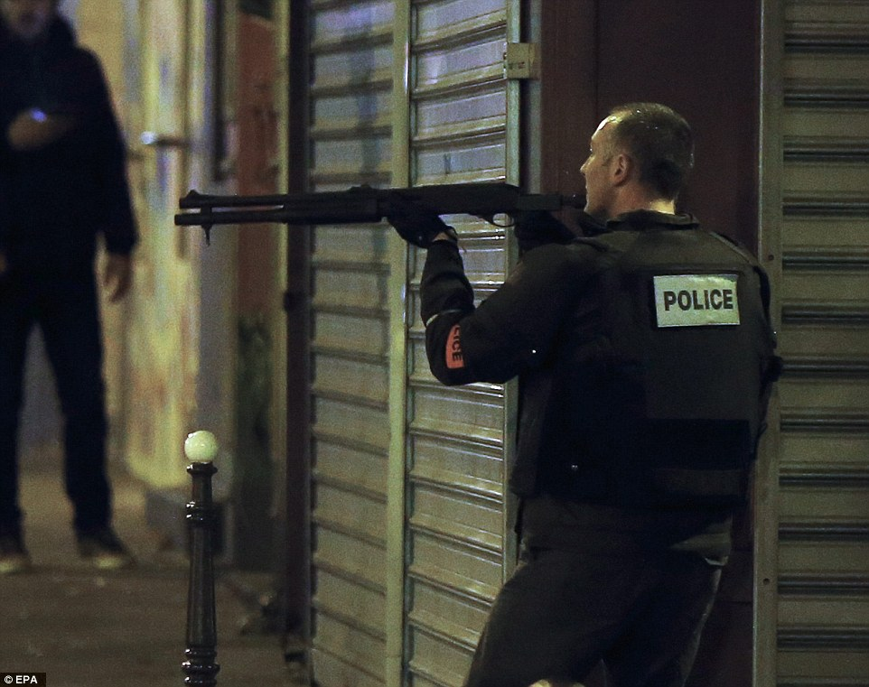 A French police officer takes cover while on the lookout for the shooters who attacked the restaurant 'Le Petit Cambodge'