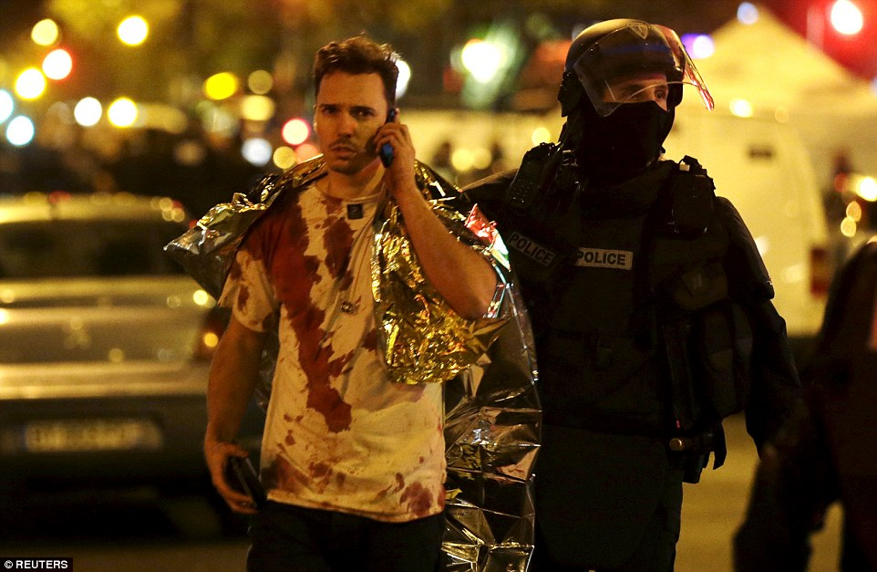 Bloodied: A French policeman assists a blood-covered victim near the Bataclan concert hall following the attacks