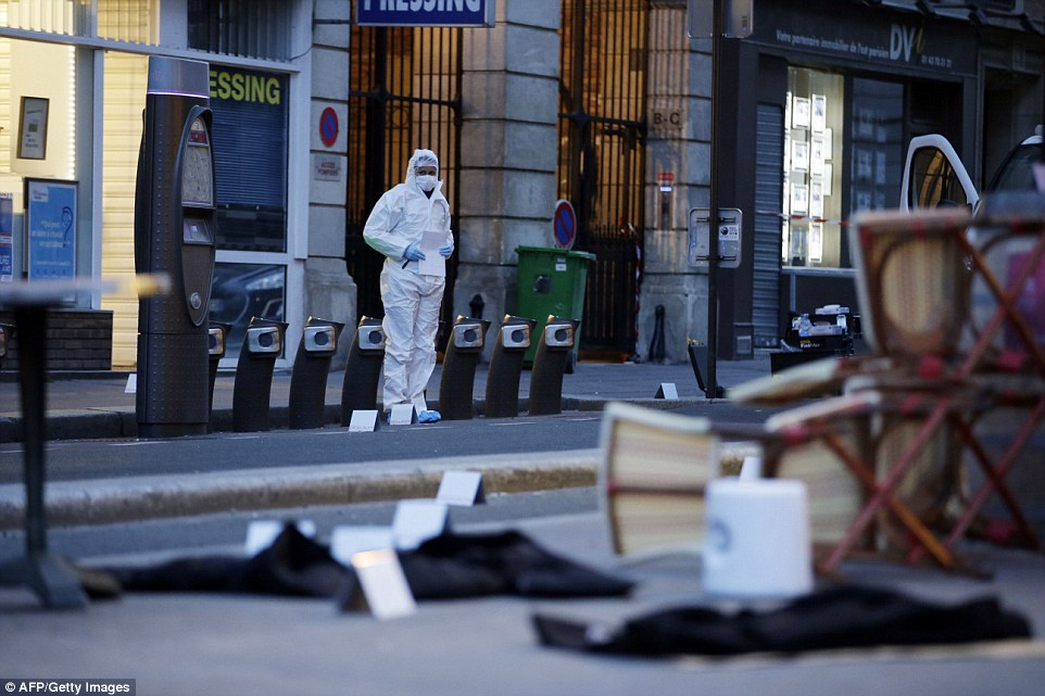 A forensic scientist inspects the scene outside of the Cafe Bonne Biere on Rue du Faubourg du Temple in Paris on Saturday