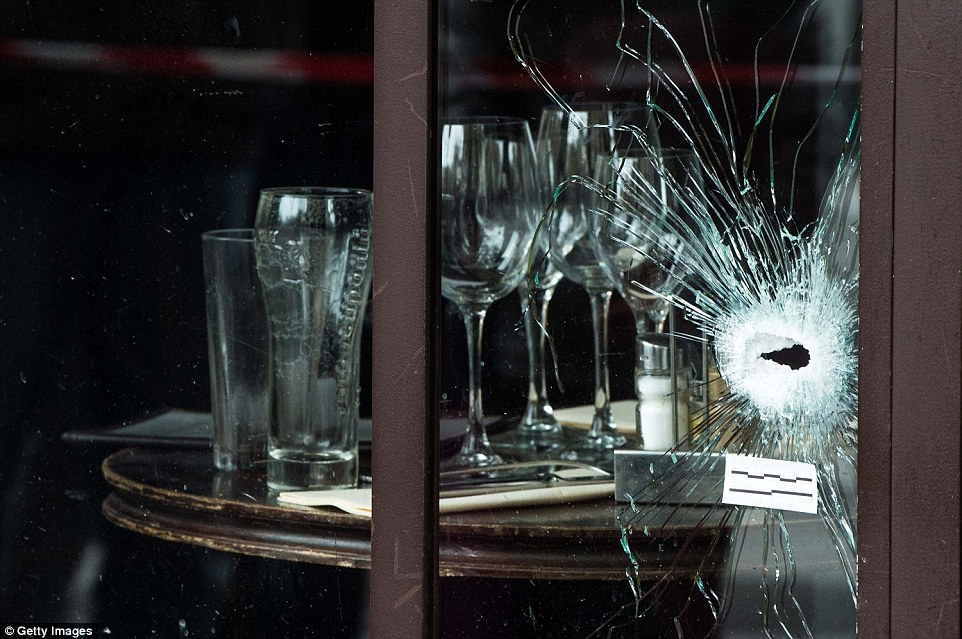 Bullet holes are seen on the windows of the Cafe Bonne Biere restaurant near a table of cutlery and wine glasses