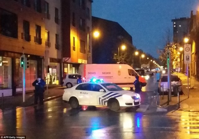 Belgian anti-terror police launched a series of raids in the Brussels area after three suspects were arrested as they attempted to cross the border from France. A bomb disposal unit and police car is seen in the Molenbeek district of Brussels last night as the arrests were made