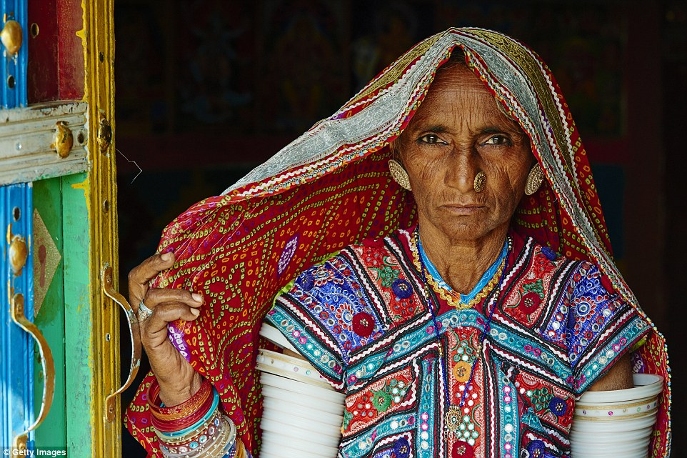 This village woman shows off her colourful outfit (above) in Gujarat, west India. She wears bangles up to her arms  to complete the outfit