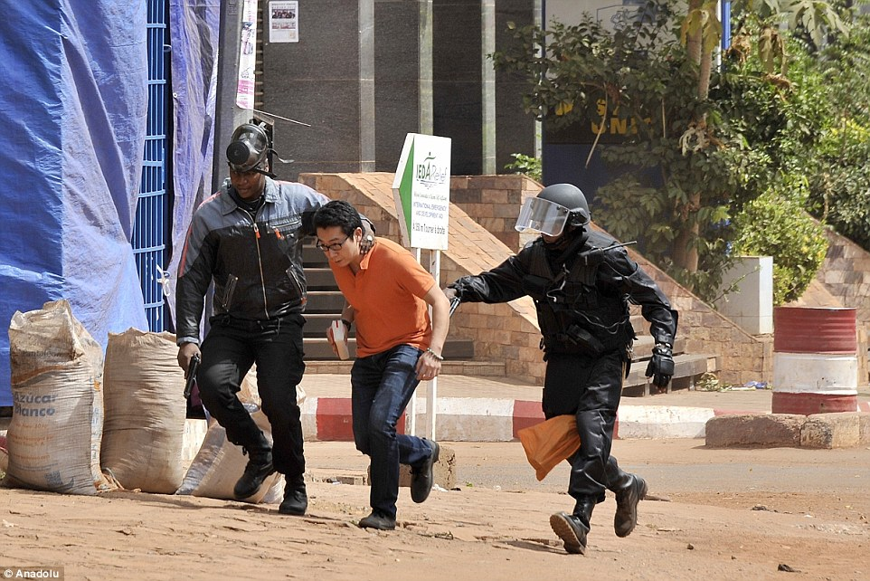 Malian special forces lead one hostage survivor out of the hotel and along the road near the horrific scene