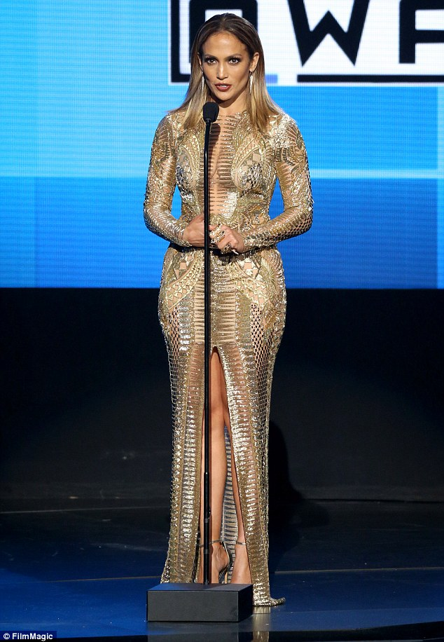Stunning: The host's skin-tight gold dress showed off her long legs and cleavage