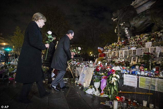 Francois Hollande and German Chancellor Angela Merkel pay their respects to the victims of the attacks
