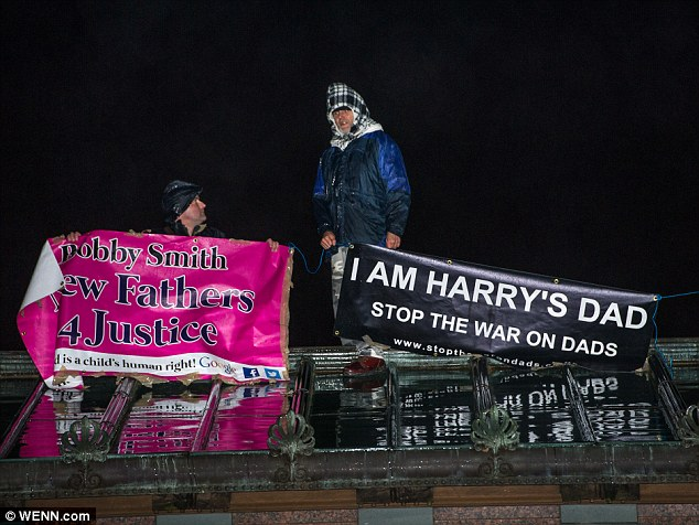 The men scaled the roof of the Queen's Gallery, a public art gallery at Buckingham Palace, central London, at around 4pm and held a banner which read: 'I am Harry's dad' and another which said 'New Fathers 4 Justice'