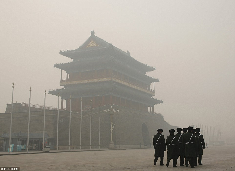 Soldiers walk past Zhengyangmen Gate as they patrol in Tiananmen Square during a heavily polluted day in Beijing, China today