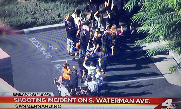 People are pictured being evacuated from the car park after the shooting at 11.30am Pacific Time