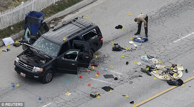 Above, an officer looks over the evidence near the remains of a SUV involved in the police shootout in San Bernardino, California