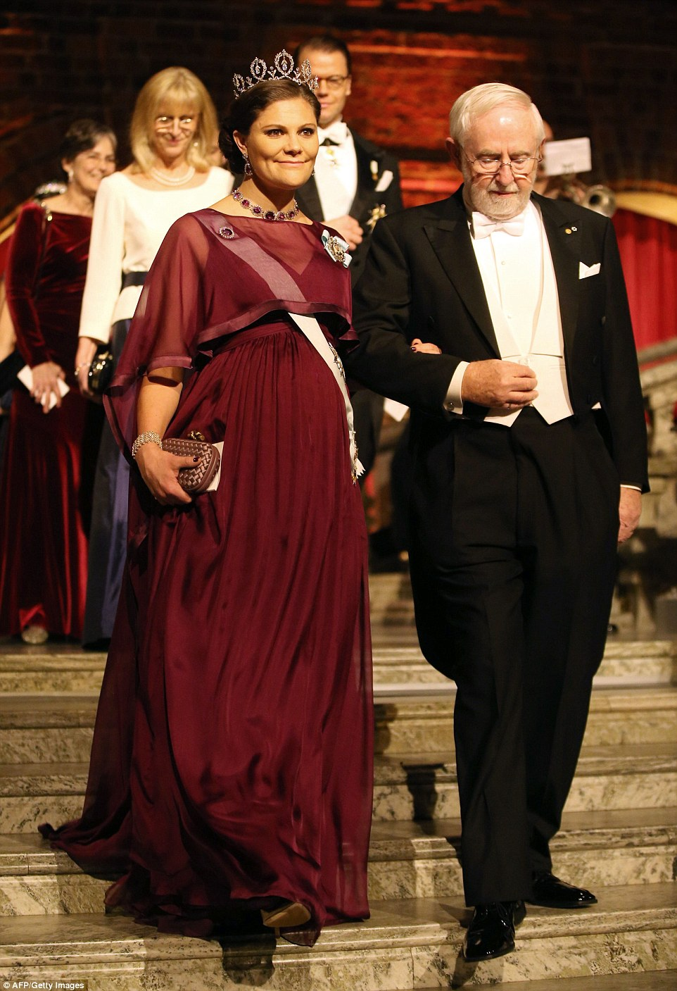 Pregnant Crown Princess Victoria showed off her baby bump in an elegant skirt and sheer top, accessorised with the dazzling Connaught Diamond Tiara, as she entered on the arm ofNobel Chemistry Prize 2015 co-winner Canadian Arthur B McDonald wearing white tie and tails