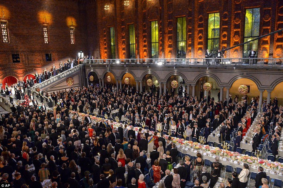Guests at the glittering bash were upstanding as the guests of homour seated at the long central table, bedecked with blooms, made their progress down the stately marble stairs of Stockholm's City Hall