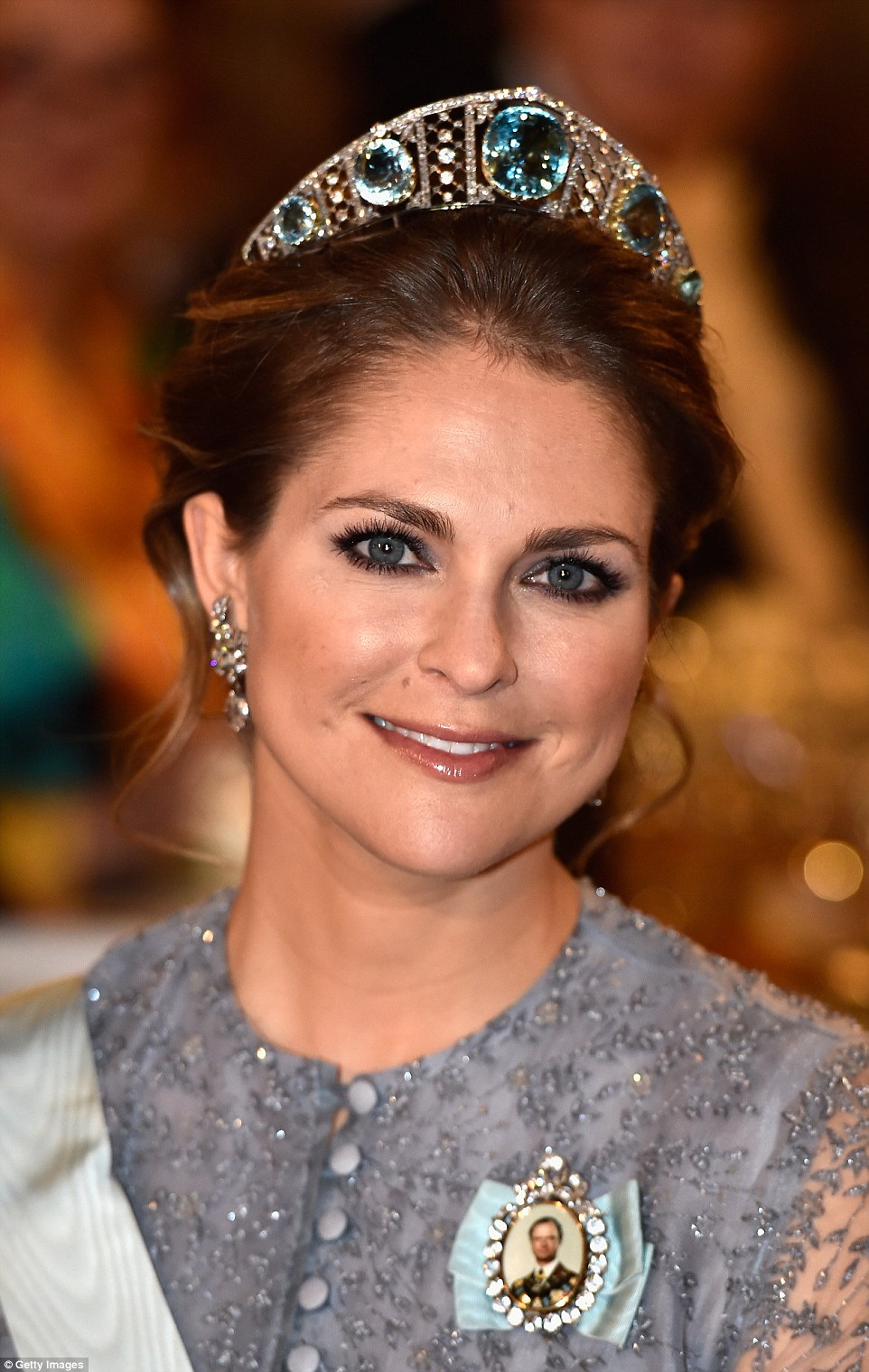 Princess Madeleine smiles for the camera in natural makeup and a chic updo to accentuate her domed tiara with the country's rarely seen Aquamarine Kokoshnik tiara made up of diamond lattices holding five huge aquamarines in place