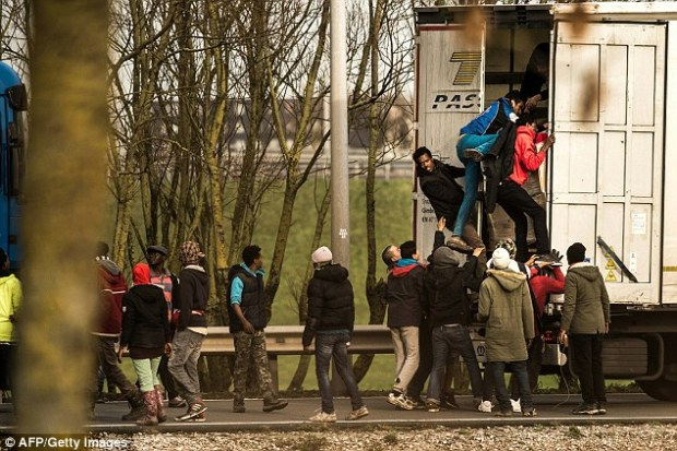 Migrants clamber on board a lorry waiting in traffic at Calais yesterday, which also saw 1,000 try to storm the Channel Tunnel in what police called an 'unprecentented' security breach
