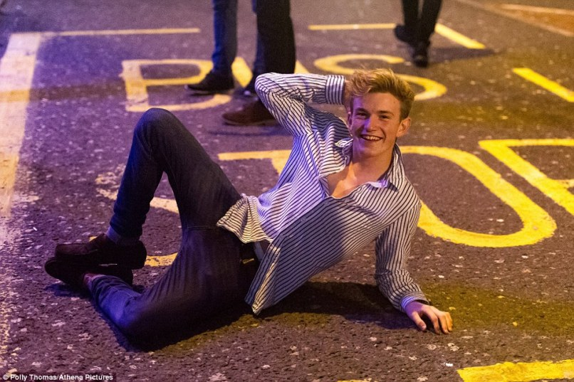 Posed: A man appears to enjoy having his photograph taken as he lay on the ground in a bus stop in Cardiff