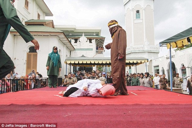 After her punishment was over the young woman collapsed and could be seen lying on the floor in agony