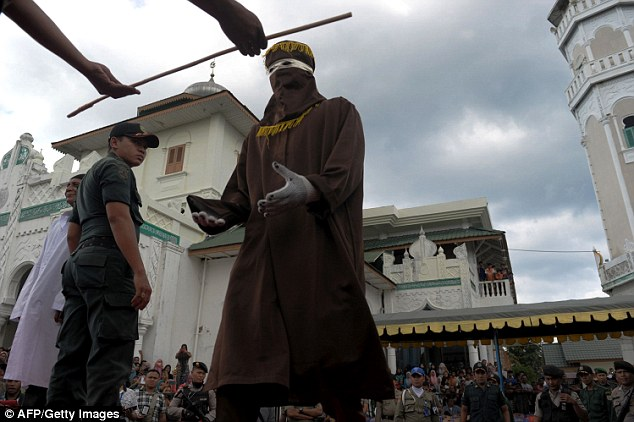 The masked man, a member of the Sharia Police receives the cane he uses to carry out the public punishment