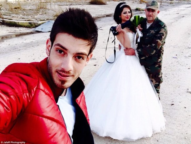 Sending a message: The photographer (pictured posing with the newlyweds) said the photoshoot was 'proof that life goes on, silently'