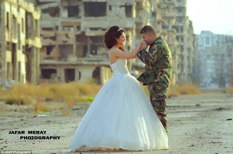Act of love: At another point in the shoot, the woman gazed lovingly at her spouse - a Syrian Army soldier - as he gently kissed her hands