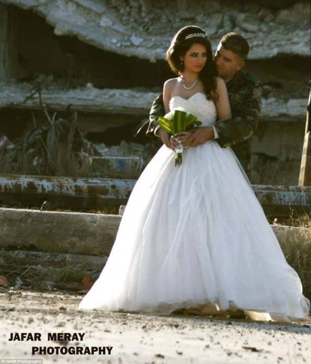 Touching embrace: Dressed in a stunning white gown, the bride looked emotional as her husband embraced her tenderly from behind