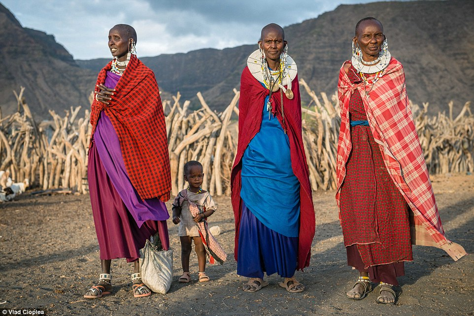 Colourful women and a small child stand out on the golden plains in the Natron Lake Village thanks to their flamboyant outfits and jewellery