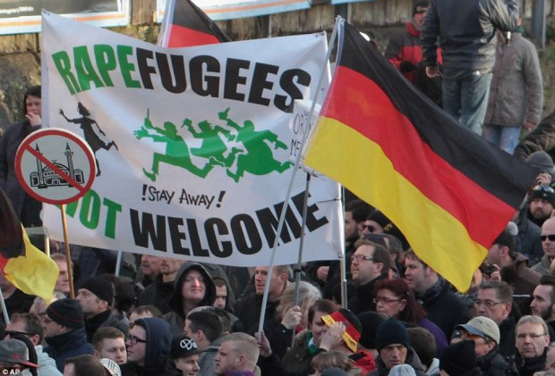 """Right-wing demonstrators hold a sign """"Rapefugees not welcome - !Stay away!"""" and a sign with a crossed out mosque as they march in Cologne"""
