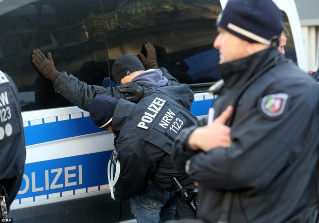 Police search a right-wing demonstrator outside the main station in Cologne where more than 100 women were assaulted by mob of migrants on New Year's Eve