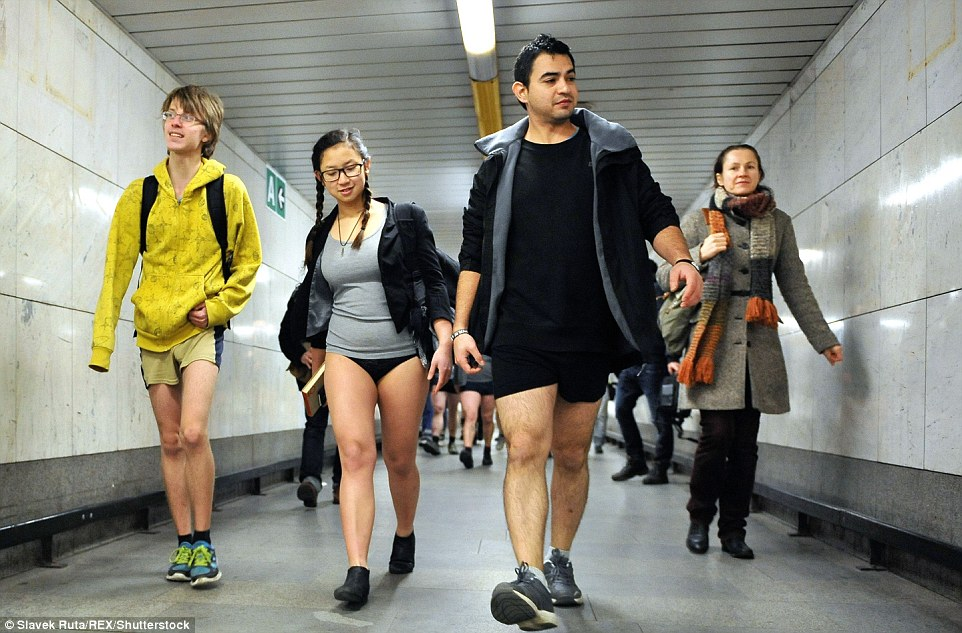 Braving the cold: These travellers wear coats but no trousers for the ride, looking comfortable inside the station where it's warmer