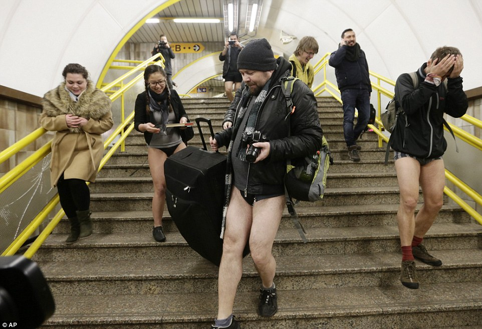 Passengers not wearing pants help a woman with her luggage as they take part in the No Pants Subway Ride in Prague, Czech Republic