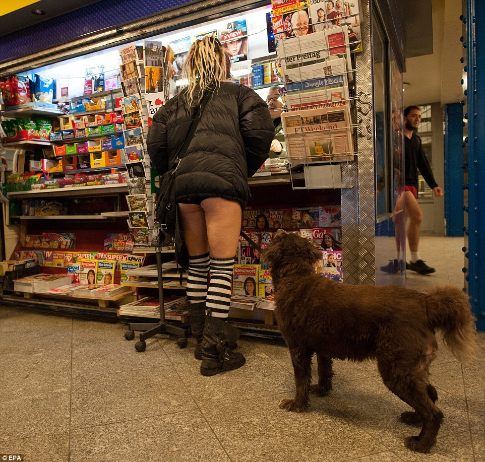 A woman wearing underpants stands in the Frankfurter Tor underground station, acting causally with her dog, also not wearing trousers