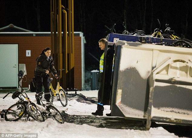 Los agentes de policía en la estación de paso de frontera noruega en Storskog lanzan bicicletas usadas para cruzar la frontera de Rusia en un contenedor de reciclaje