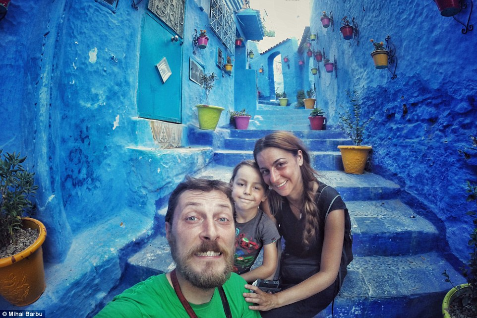 The Barbu family pose on the vibrantly coloured streets of the blue city of Chefchouaen, Morocco