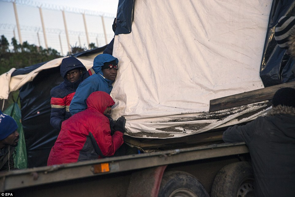 Migrants use all their strength to push their makeshift wooden shack on to the back of a trailer to be taken elsewhere in Calais