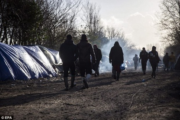 Migrants walk along the shacks and tents of the makeshift migrant camp in Grande-Synthe near Dunkirk. The refugee camp in Grande-Synthe counts an estimated 3,000 residents mostly composed of Kurds from Iraq