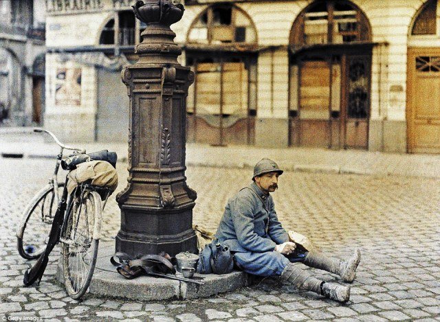 A French soldier has lunch in front of a damaged library in a square in Reims, in north-eastern France on 1 April 1917