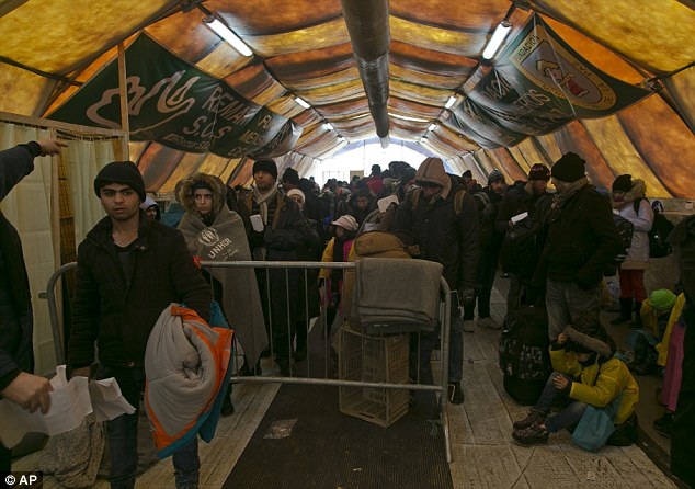 Migrants wait inside a tent to keep warm before departing from the registration camp after crossing from the Macedonian border into Serbia, in Presevo, Serbia