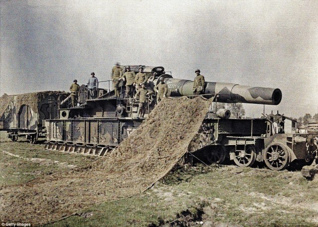 Eight French soldiers stand on top of a 370mm railway gun which they are camouflaging on 5 September 1917