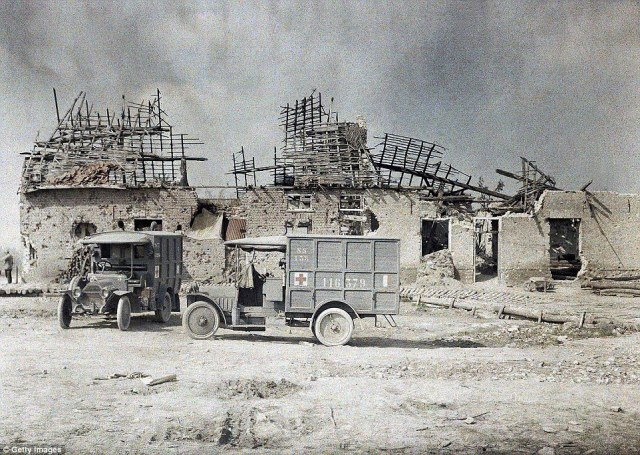 Two ambulance vehicles in front of a building near the village of Boezinge, north of the city of Ypres, that was devastated by artillery fire